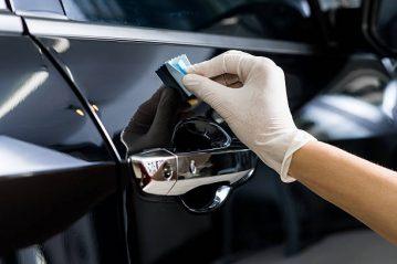 Closeup of hand coating black car door